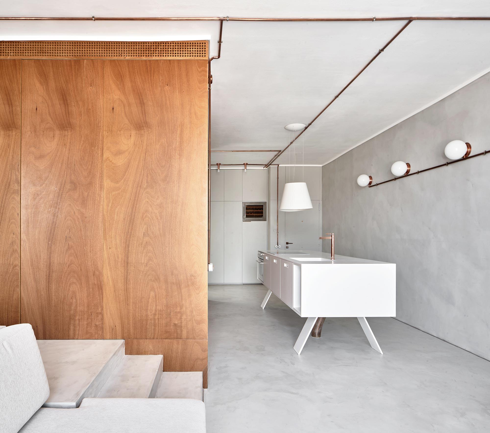 Mueble de cocina en isla blanco y armario de madera visto desde el sofa, espacio de diseño con suelos y paredes de cemento