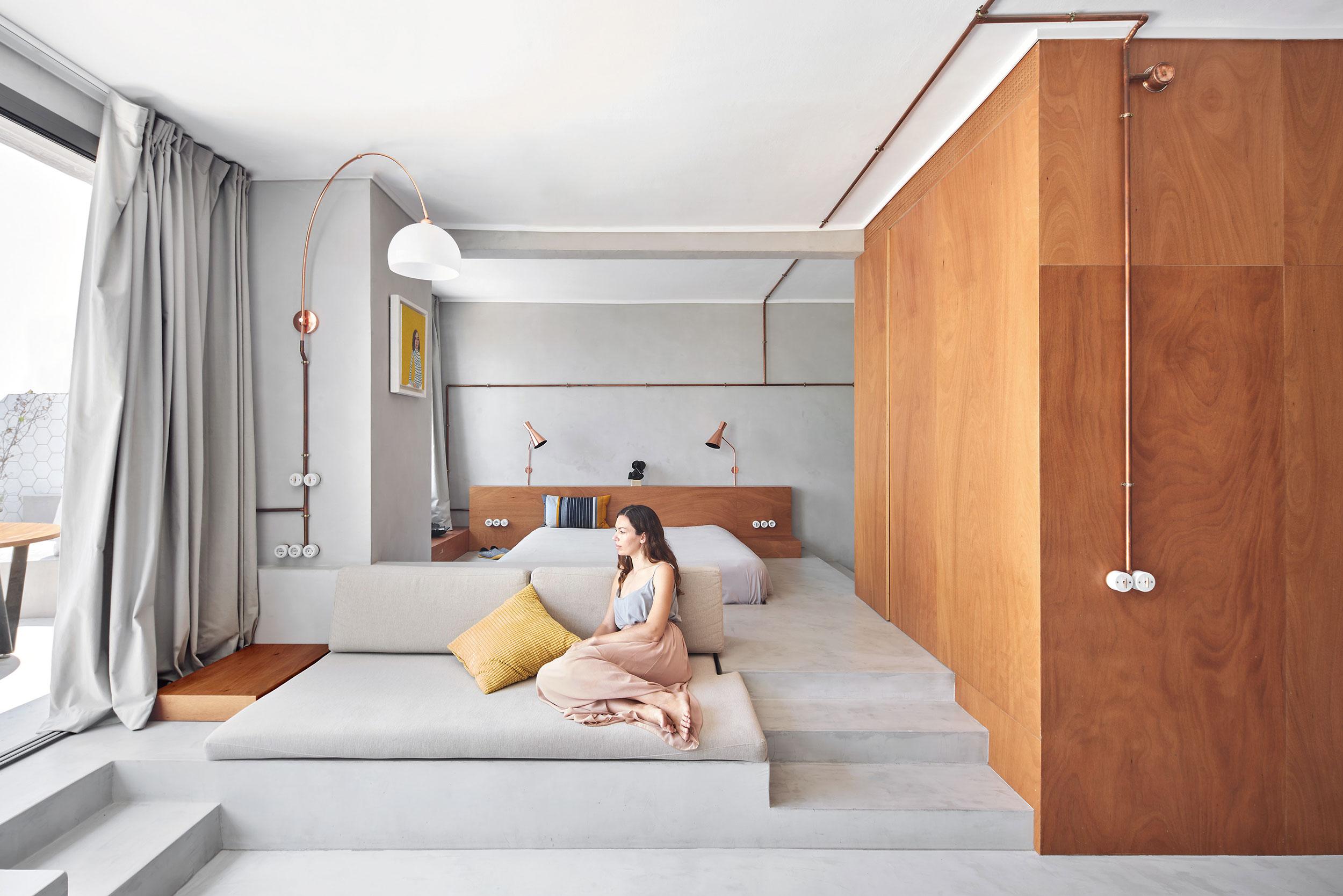 persona sentada confortablemente en un sofa construido con armarios de madera de okume y cortinas de sastrería