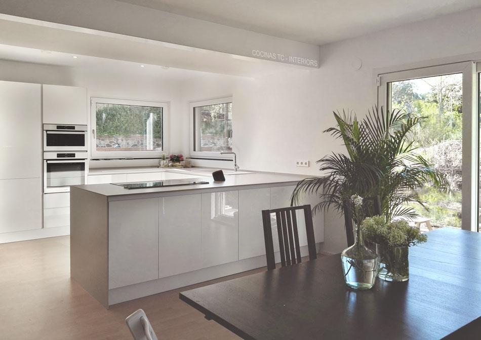 Muebles de cocina TC-Interiors, en acabado blanco, con encimera Neolith gris claro, y plantas en en Valldoreig, Barcelona