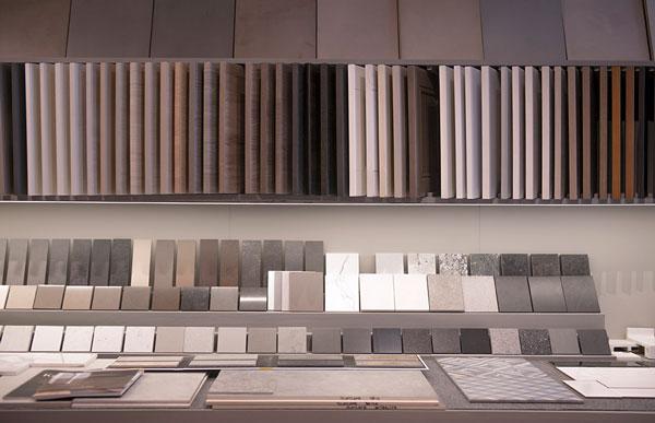 Muestras de materiales como pavimentos cerámicos o de madera , encimeras y muebles de cocina, ordenados por gama de colores y tonos.