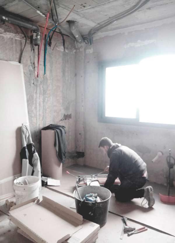 Albañil de TC-Interiors cortando baldosas de suelo de reforma de cocina